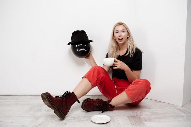 Jovem mulher loira bonita segurando balão preto no chapéu, sentada no chão, bebendo café sobre parede branca