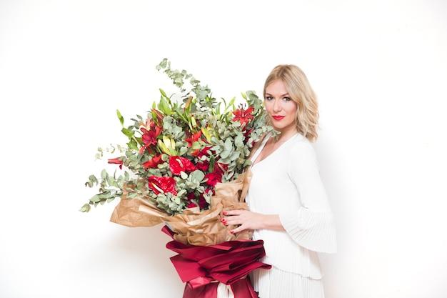 Jovem mulher loira bonita segurando um grande buquê de flores coloridas contra a parede