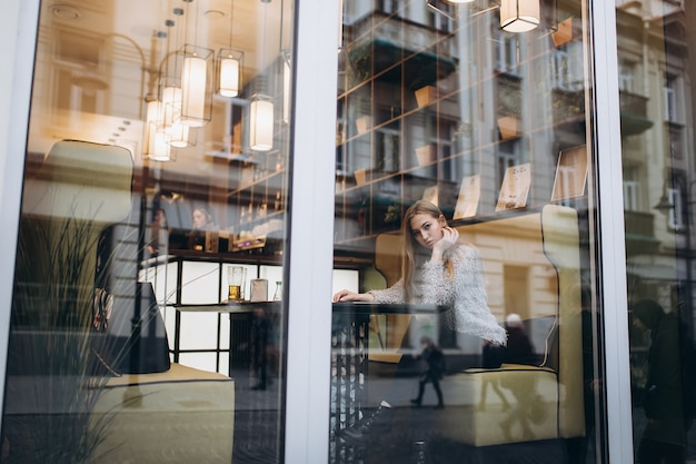 Jovem mulher loira bonita sentada em um café no centro da cidade
