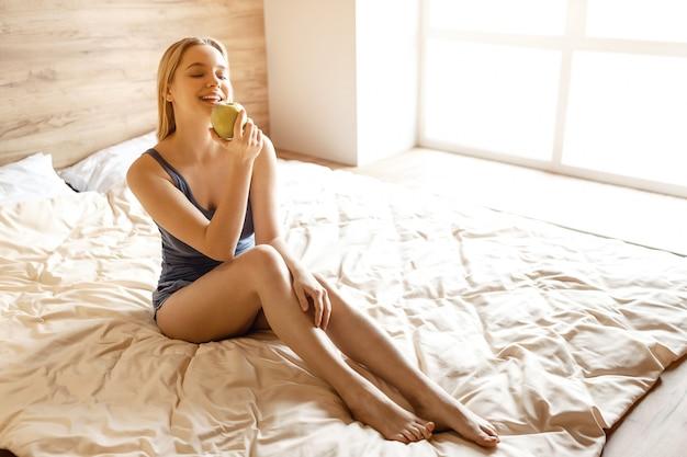 Jovem mulher loira bonita sentada na cama de manhã. ela segura uma grande maçã verde saborosa na mão e olha para ela. modelo posando. luz do dia.