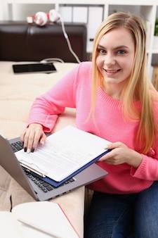 Jovem mulher loira bonita sente-se na sala de trabalho no laptop