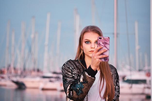 Jovem mulher loira bonita tirando fotos com um smartphone