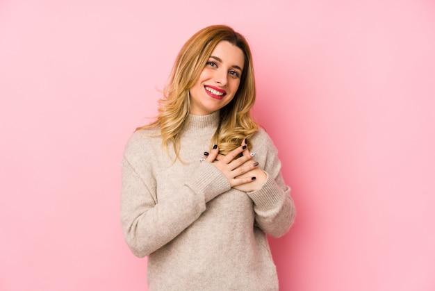 Jovem mulher loira bonita vestindo um suéter tem expressão amigável, pressionando a palma da mão no peito