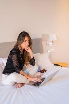 Jovem mulher loira branca sentada na cama em casa assistindo ao noticiário online