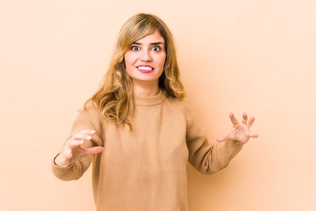 Jovem mulher loira caucasiana chateada, gritando com as mãos tensas.