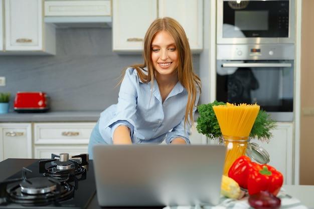 Jovem mulher loira caucasiana com cabelo comprido usando laptop em uma cozinha
