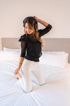 Jovem mulher loira caucasiana com fones de ouvido dançando e curtindo música em cima da cama em casa