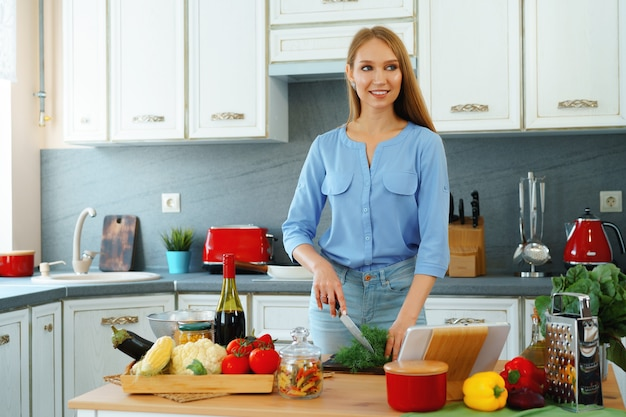 Jovem mulher loira caucasiana cortando vegetais para salada na cozinha