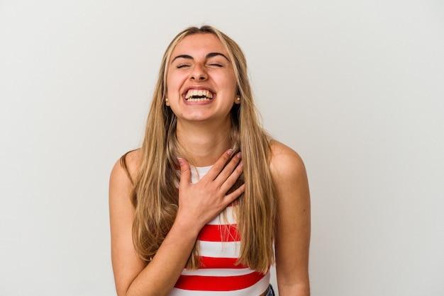 Jovem mulher loira caucasiana em fundo branco isolado ri alto, mantendo a mão no peito.