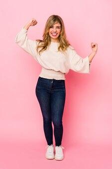 Jovem mulher loira caucasiana em pé sobre uma parede rosa comemorando um dia especial, pula e levanta os braços com energia.