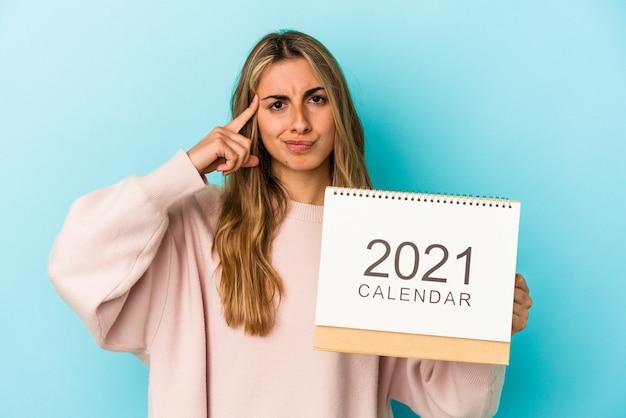 Jovem mulher loira caucasiana fura um calendário apontando o templo com o dedo, pensando, focado em uma tarefa.