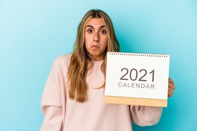 Jovem mulher loira caucasiana fura um calendário isolado encolhe os ombros e abre os olhos confusos.