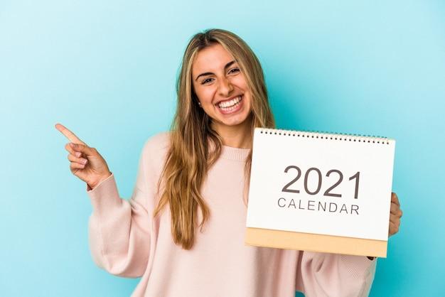 Jovem mulher loira caucasiana fura um calendário isolado, sorrindo e apontando de lado, mostrando algo no espaço em branco.