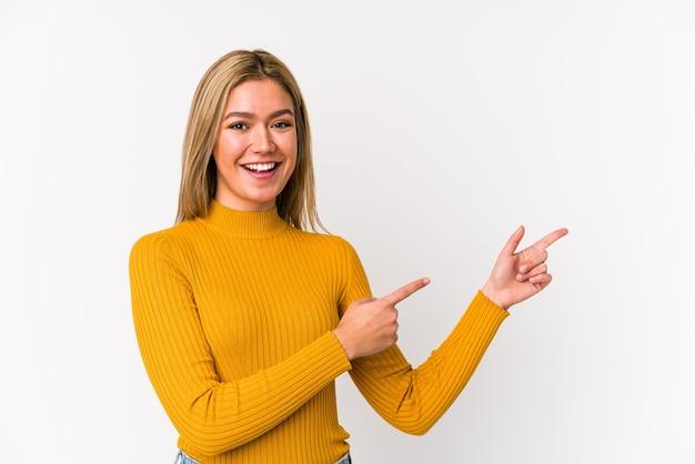 Jovem mulher loira caucasiana isolada animado apontando com os indicadores de distância.