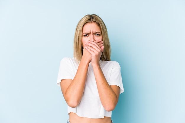 Jovem mulher loira caucasiana isolada boca coning com as mãos parecendo preocupadas.