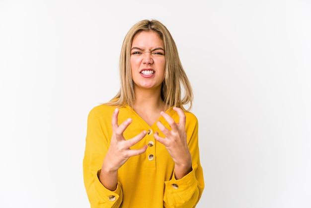 Jovem mulher loira caucasiana isolada chateada gritando com as mãos tensas.