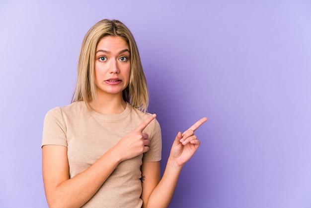 Jovem mulher loira caucasiana isolada chocada apontando com o dedo indicador para um espaço de cópia.
