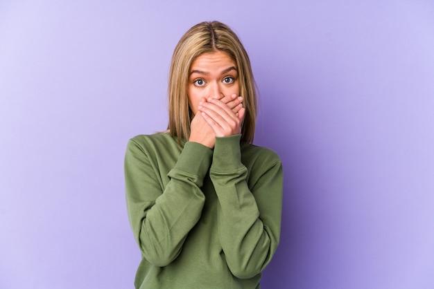 Jovem mulher loira caucasiana isolada chocada cobrindo a boca com as mãos.