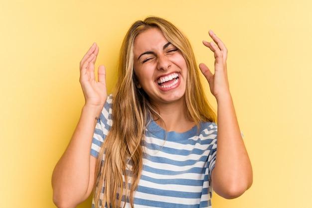 Jovem mulher loira caucasiana isolada em fundo amarelo alegre rindo muito. conceito de felicidade.