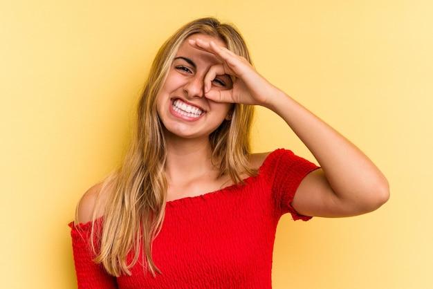 Jovem mulher loira caucasiana isolada em fundo amarelo animada mantendo o gesto de aprovação no olho.