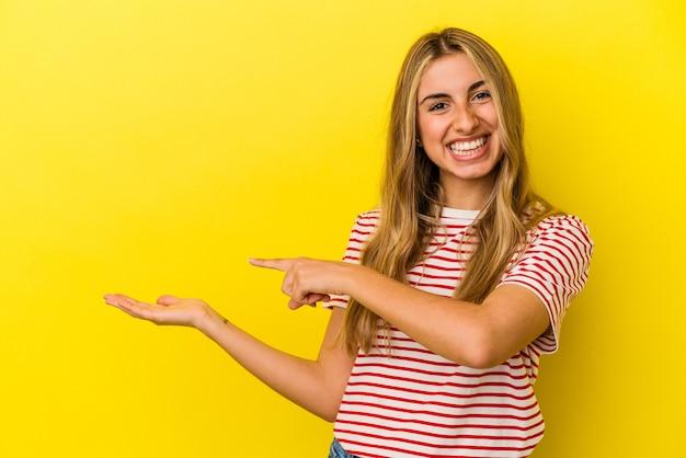 Jovem mulher loira caucasiana isolada em fundo amarelo animado segurando um espaço de cópia na palma da mão.