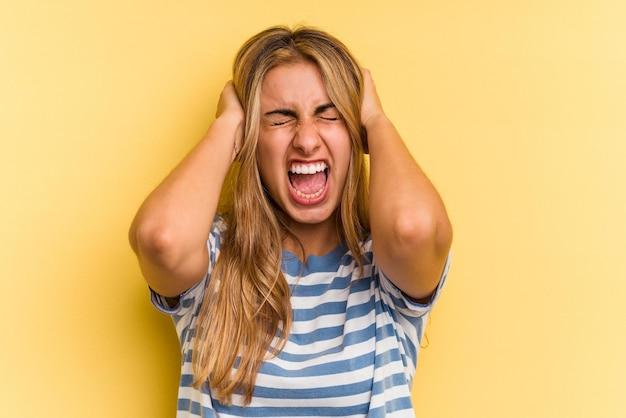 Jovem mulher loira caucasiana isolada em fundo amarelo, cobrindo as orelhas com as mãos, tentando não ouvir o som muito alto.