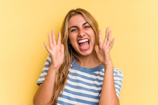 Jovem mulher loira caucasiana isolada em fundo amarelo, comemorando uma vitória ou sucesso, ele fica surpreso e chocado.