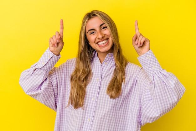 Jovem mulher loira caucasiana isolada em fundo amarelo indica com os dois dedos anteriores mostrando um espaço em branco.