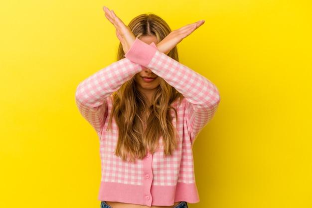 Jovem mulher loira caucasiana isolada em fundo amarelo, mantendo os dois braços cruzados, conceito de negação.