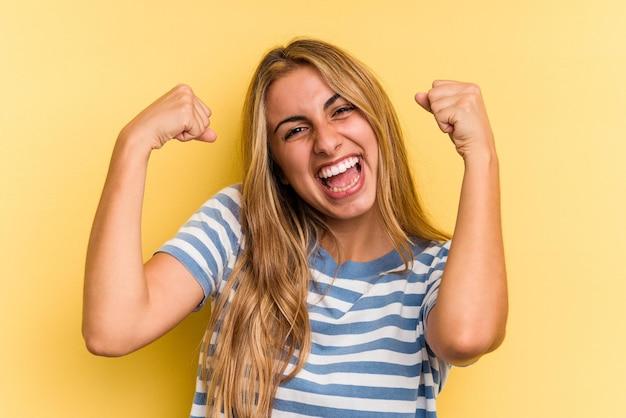 Jovem mulher loira caucasiana isolada em fundo amarelo mostrando força gesto com os braços, símbolo do poder feminino