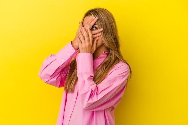 Jovem mulher loira caucasiana isolada em fundo amarelo piscar por entre os dedos assustados e nervosos.