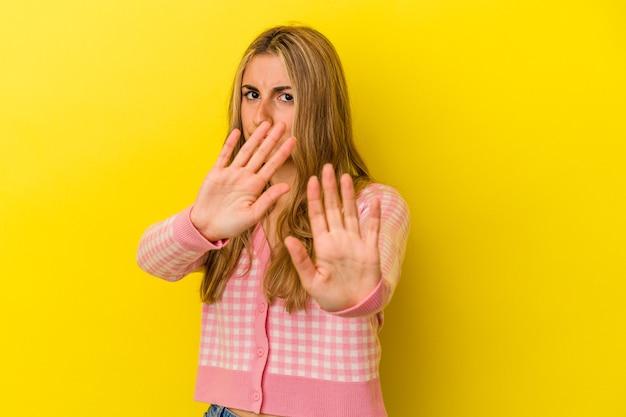 Jovem mulher loira caucasiana isolada em fundo amarelo, rejeitando alguém mostrando um gesto de nojo.