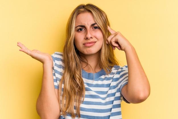 Jovem mulher loira caucasiana isolada em fundo amarelo, segurando e mostrando um produto por lado.