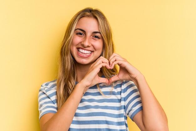 Jovem mulher loira caucasiana isolada em fundo amarelo, sorrindo e mostrando uma forma de coração com as mãos.