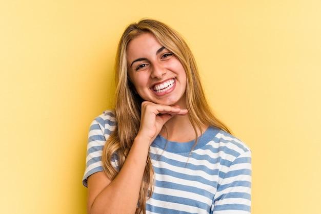 Jovem mulher loira caucasiana isolada em fundo amarelo, sorrindo feliz e confiante, tocando o queixo com a mão.