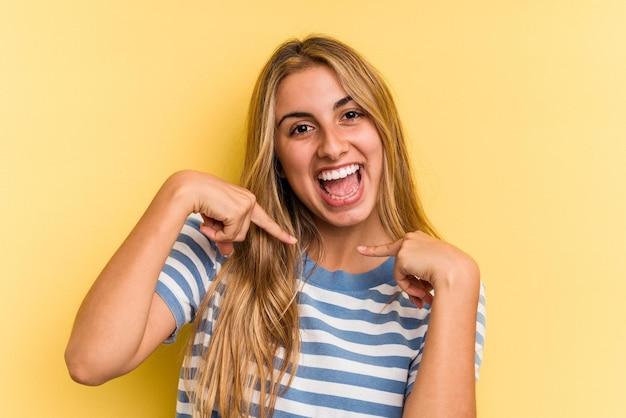 Jovem mulher loira caucasiana isolada em fundo amarelo surpreendeu apontando com o dedo, sorrindo amplamente.