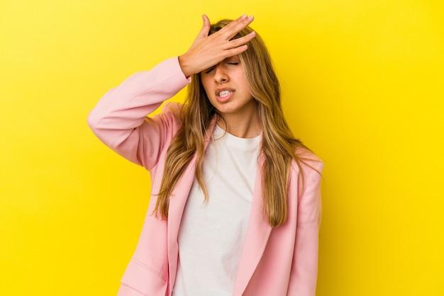 Jovem mulher loira caucasiana isolada em fundo amarelo, tocando as têmporas e tendo dor de cabeça.
