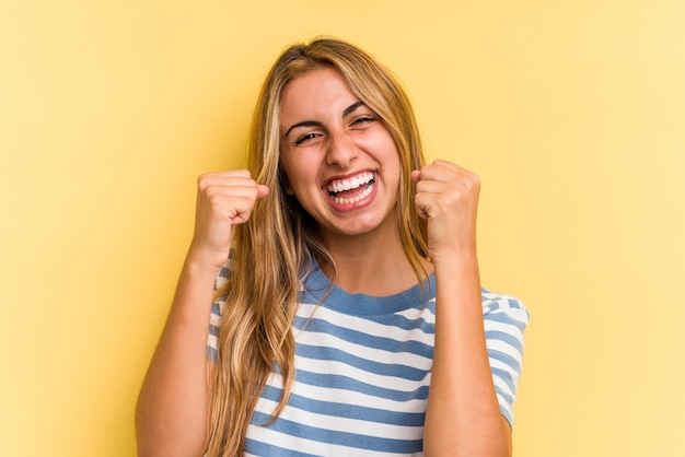Jovem mulher loira caucasiana isolada em fundo amarelo torcendo despreocupada e animada. conceito de vitória.