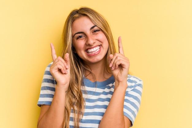 Jovem mulher loira caucasiana, isolada em um fundo amarelo, apontando para diferentes espaços de cópia, escolhendo um deles, aparecendo com o dedo.