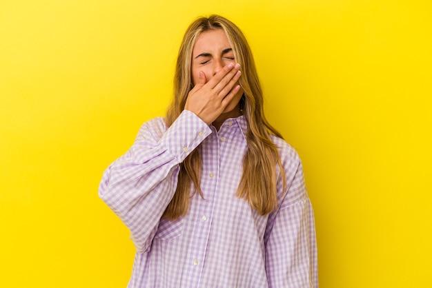 Jovem mulher loira caucasiana isolada em um fundo amarelo, bocejando, mostrando um gesto cansado, cobrindo a boca com a mão.