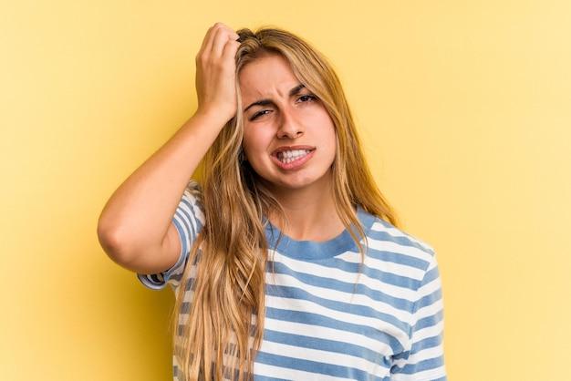 Jovem mulher loira caucasiana, isolada em um fundo amarelo, cansada e com muito sono, mantendo a mão na cabeça.