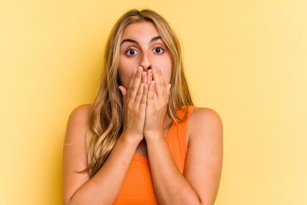 Jovem mulher loira caucasiana, isolada em um fundo amarelo chocada, cobrindo a boca com as mãos.
