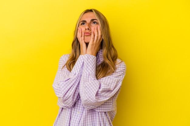 Jovem mulher loira caucasiana isolada em um fundo amarelo, chorando e chorando desconsoladamente.