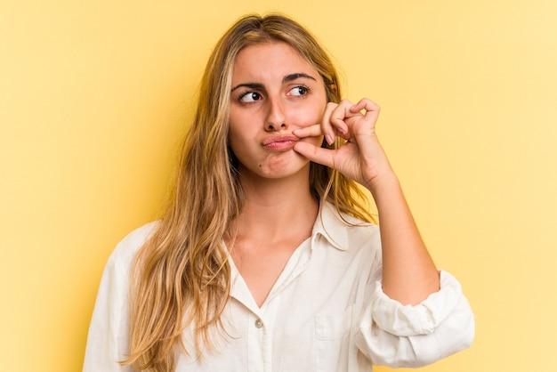 Jovem mulher loira caucasiana, isolada em um fundo amarelo com os dedos nos lábios, mantendo um segredo.