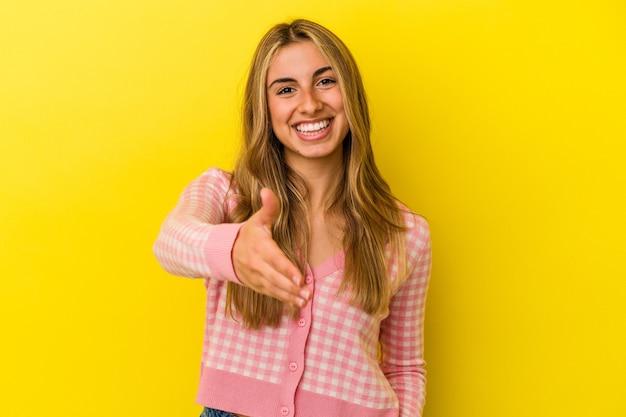 Jovem mulher loira caucasiana isolada em um fundo amarelo, esticando a mão na câmera em um gesto de saudação.