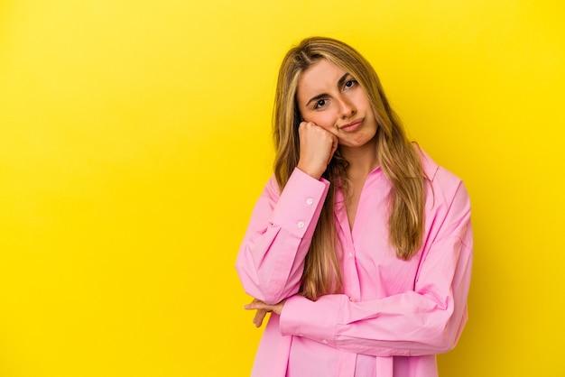Jovem mulher loira caucasiana isolada em um fundo amarelo que se sente triste e pensativa, olhando para o espaço da cópia.