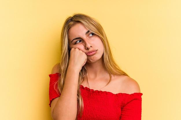 Jovem mulher loira caucasiana, isolada em um fundo amarelo, que se sente triste e pensativa, olhando para o espaço da cópia.