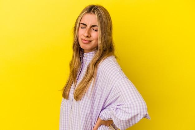 Jovem mulher loira caucasiana isolada em um fundo amarelo, sofrendo de dor nas costas.