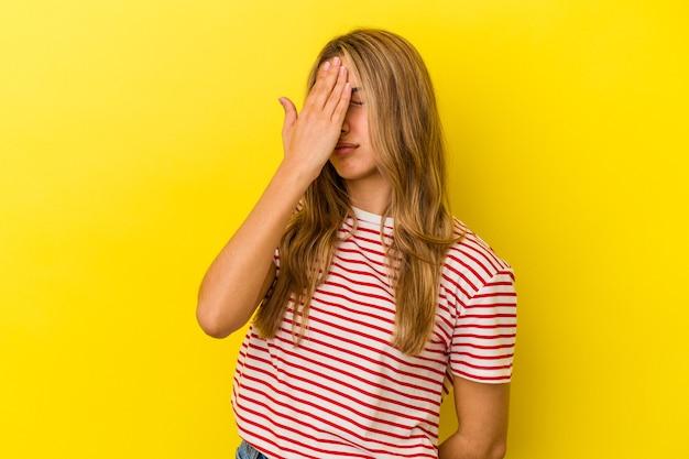 Jovem mulher loira caucasiana isolada em um fundo amarelo, tendo uma dor de cabeça, tocando a frente do rosto.