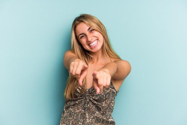 Jovem mulher loira caucasiana isolada em um fundo azul, apontando para a frente com os dedos.